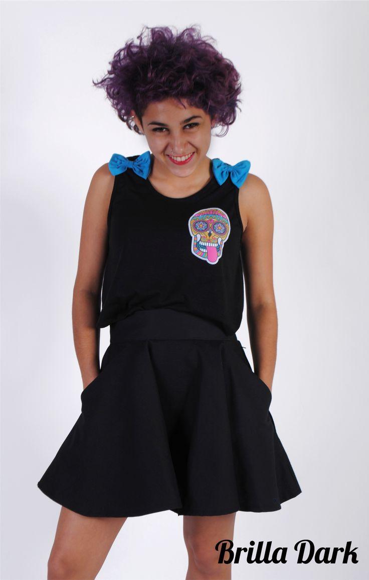 Musculosa de modal con apliques de moños y calavera + Pollera plato, tipo skater, de gabardina color negro, con bolsillos