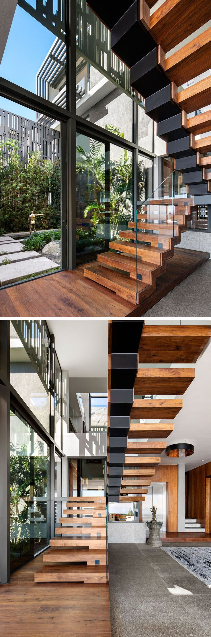 Modern wood and black metal stairs lead up to the upper floor of the home, while glass railings appear invisible and allow the view of the courtyard to be uninterrupted.
