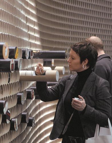 """""""Designers from D'Art Design Gruppe created paper coasters that featured hand-sketched fictional projects as well as renderings of actual Projektpilot works, then placed them inside three dozen of the cardboard tubes for visitors to inspect."""":"""