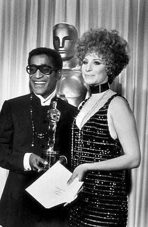 American singer and actor Sammy Davis Jr. (1925-1990) posed with Barbra Streisand as he accepted the Oscar on behalf of Leslie Bricusse, who received the award for the song 'Talk to The Animals' from the film, 'Doctor Doolittle.'