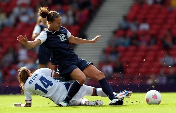 Lauren Cheney of USA is tackled by Louisa Necib of France during the Women's Football first round Group G Match of the London 2012 Olympic Games between United States and France, at Hampden Park on July 25, 2012 in Glasgow, Scotland