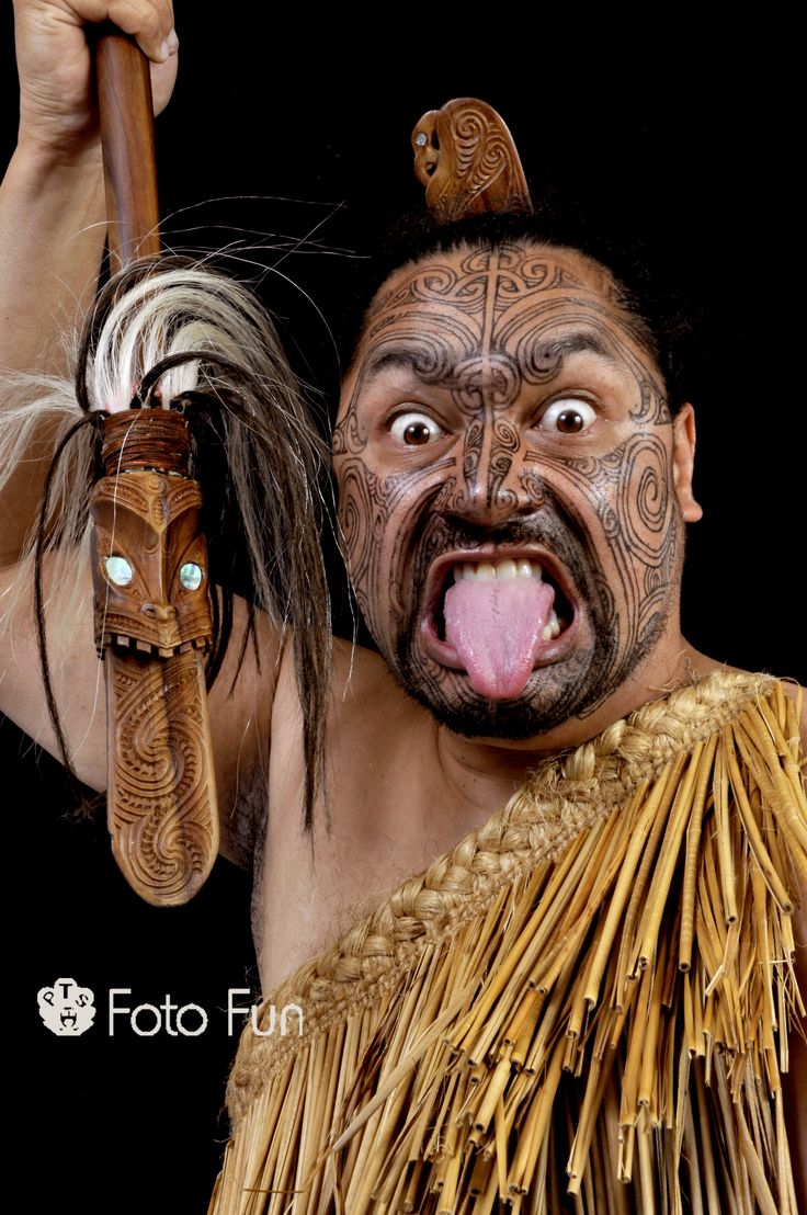 Maori man with weapon and traditional war position and gesture