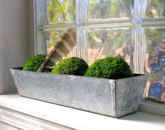 Great galvanized planter box would be right at home in an industrial, primitive, or farmhouse rustic decor. Sized just right to sit on a window sill, this cool metal container could be used for other purposes, too: to hold napkins & silverware on your counter, hand towels or washcloths in a bathroom, files in your office, or supplies in your craft room. There is some rust inside, but it has been sprayed with matte-finish sealer. Moss balls, feather not included.    16 long x 5 wide at top...
