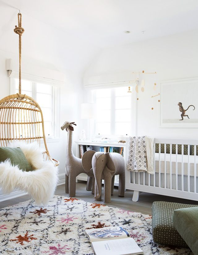 Cozy nursery with a colorful rug, a hanging chair with a faux fur, stuffed animals and a white childrens bed.