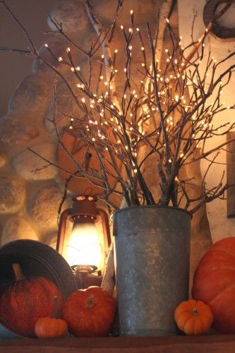 Fall decor- pumpkins, lantern, and lighted branches. fall falldecor fallmantel