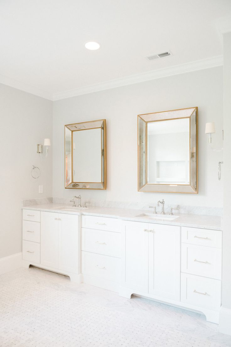 White bathroom caninets, Carrera Countertop and gold mirrors. Classic and  stylish. Master Bathroom by Studio McGee