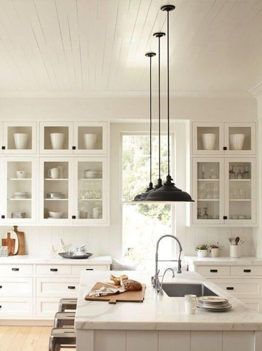 White kitchen mixed with black light fixtures, glass cabinets and accent of wood. / Cuisine blanche agencé avec des luminaires noirs, des armoires en verre et des accents de bois.