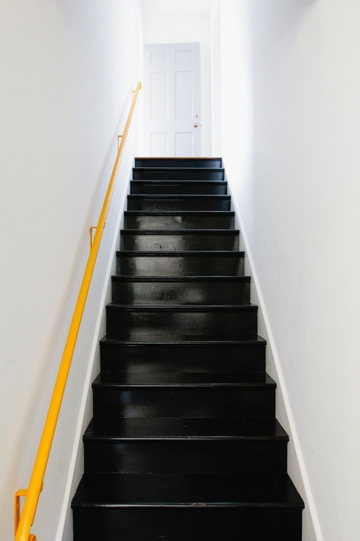 Black painted back stairs with yellow handrail #stairway #office http://www.ironageoffice.com/