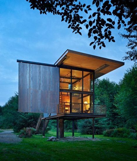 This weekend cabin in a Washington national park features a protective steel exterior that slides across its windows and a floor raised up on stilts to prevent flooding.