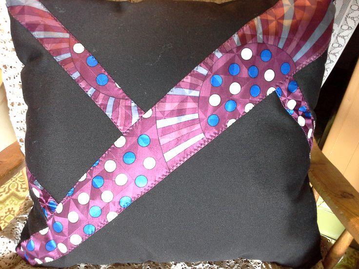 Coussin cravate fait à la main avec cravate recyclé. Coussin noir imperméabilisé aVec bourre de codelle neuf. Ce coussin est fabriqué dans un endroit sans fumé. Dimension 18 x 18 Boutique en ligne www .lestresorsdemaryse.com