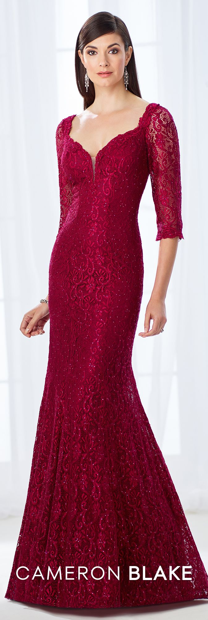 Cameron Blake 118677 - Rich and superb, this allover lace trumpet gown accented with heat set stones offers scalloped illusion lace three-quarter sleeves, a plunging curved V-neckline with an illusion modesty panel, a V-back, and a softly gathered lower skirt with a sweep train.