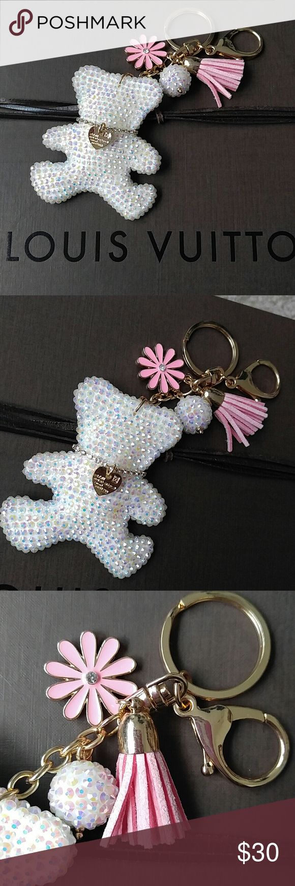 ✨Purse charm✨key ring for your Louis Vuitton purse Sparkly & cute teddy bear purse charm key ring for your Louis vuitton, michael kors, coach, Tory burch, or MCM bag! Embelished with rhinestones that sparkle, and teddy has a gold necklace. Attached is a rhinestone ball, pink tassle, and pink flower with rhinestone in the middle. Very cute! No brand, just a cute charm. Louis Vuitton Accessories Key & Card Holders