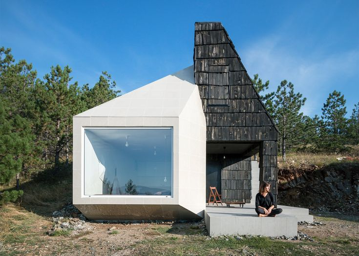 One half of this tiny mountain dwelling in western Serbia is faced in white ceramic tiles, the other is clad in dark timber shingles.