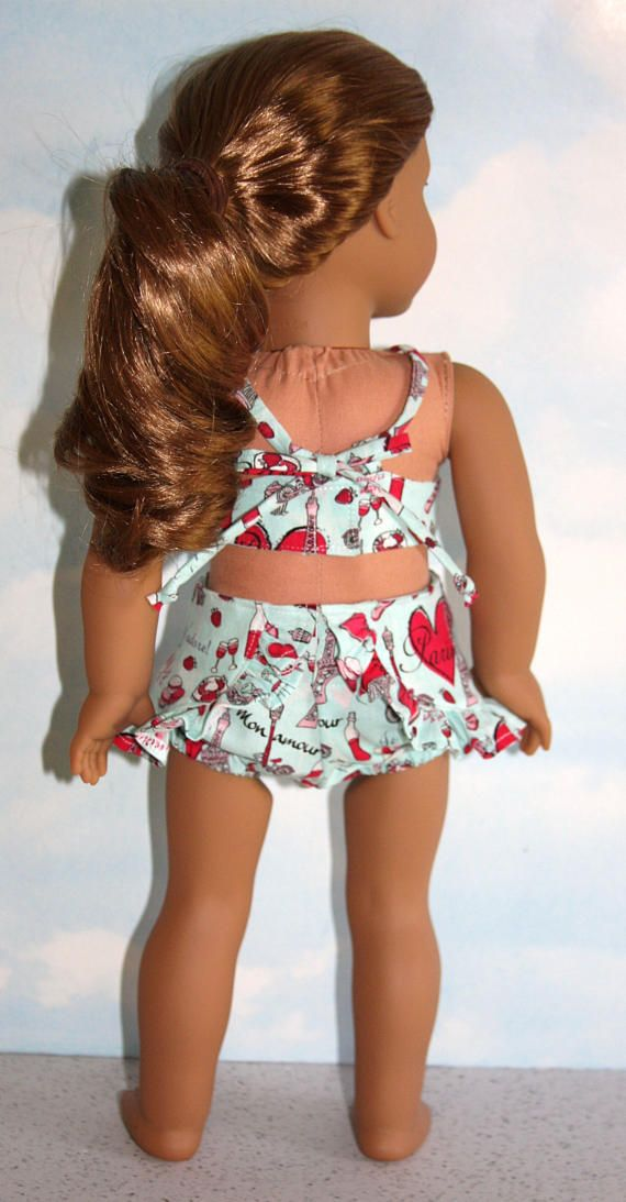 Have some fun in the sun in this sweet retro-inspired 2-piece bathing suit. Made of 100% cotton fabric with a fun Paris motif in shades of pink on an aqua background. Fully lined bodice has an attached grosgrain ribbon bow at the gathered center front; closes in back with Velcro. The