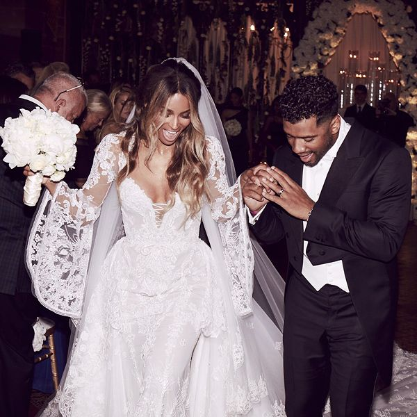 Ciara marries Russell Wilson. he singer looked stunning in a long, flowing white gown that featured a chiffon tulle skirt and detailed halter top. The NFL quarterback was dressed in head-to-toe black as he escorted his soon-to-be bride hand-in-hand across the cobblestone path. The couple exchanged vows in a romantic ceremony in England,