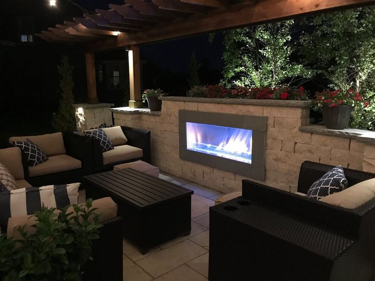 Contemporary outdoor room with fireplace. Includes a Pergola, LED Lighting, and a Natural Stone Patio. This backyard retreat is perfect for couples or entertaining. Natural Gas Fireplace. Outdoor Lighting. Backyard Lighting. #ContemporaryOutdoorLighting #outdoorentertaining #pergolafireplace