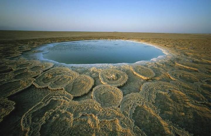 "Afar Depression in #Ethiopia, a 12-foot-wide hot springs that exists at the junction of three massive tectonic plates. It also sits on top of a volcano.  Photographer : Carsten Peter for National Geographic.  [In the Afar Depression,] spreading mid-ocean ridges forming the Red Sea and the Gulf of Aden emerge on land and meet the East African Rift.  Those circular structures around the pool are made of travertine, which is ""a volcanically heated, calcium-rich flow from hot springs."