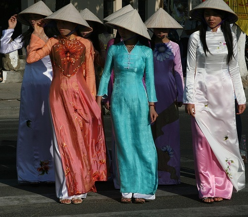 """In this image, Ao Dai - which means """"long dress"""" - is traditional Vietnamese outfit worn by both Northern and Southern Vietnamese women. (These outfits are mainly worn  in the northern area because it is receives less humidity. In the Islamic tradition, Muslim women also wear long dresses closely similar to the ones worn in Vietnam, but have different styles.(set 3)"""
