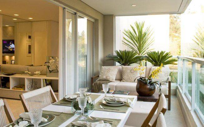 A varanda assinada por Fernanda Marques traz o conforto de um sofá com almofadas aliado aos vasos de orquídeas e palmeiras. Foto: - Divulgação
