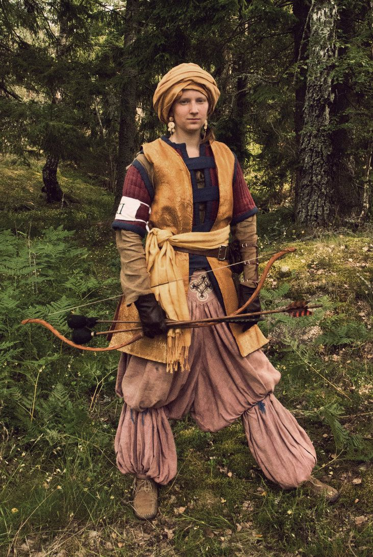 I like the pants, with the hitch? around the knee. I think it may be historical? Either way, it's a cool, and different look. I also admire the gambeson. A lot of gambesons are throw on under things, and here you can see it can be a nice part of one's kit. The hat is cool too, but I think it would fall of my head if I had to run!