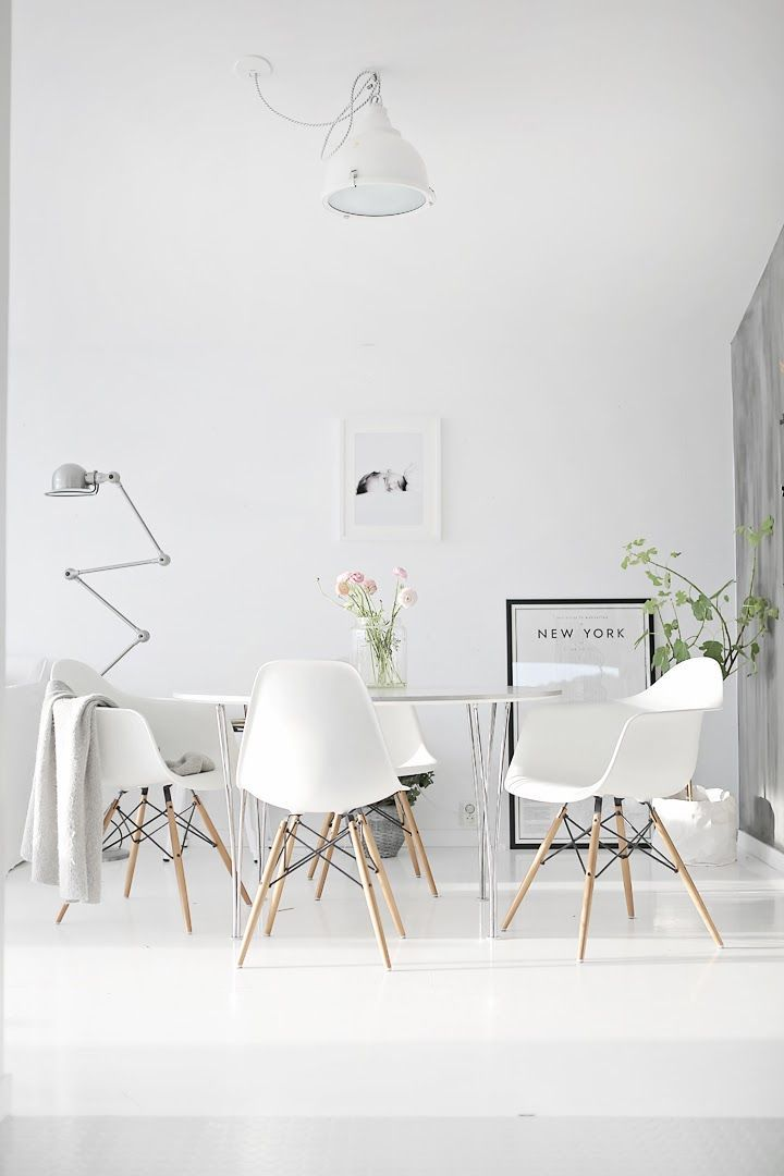 Very nice modern dining area. White, clean and cozy. The wood legs of the chairs and green plants really help bring in some warmness into this pure white space.