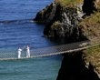Clare Leahy, left, lights Denis Broderick during a change over of the  the Olympic Torch at the Carrick-a-Rede rope bridge in county Antrim, Northern Ireland, Monday, June 4, 2012. The Olympic Torch i