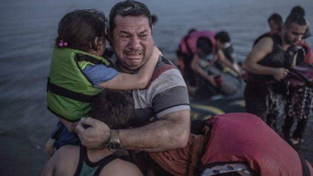 """Esta fotografía muestra al sirio Laith Majid cargando a su hijo y a su hija en sus brazos, luego de un viaje de Turquía a la isla griega de Kos en un bote inflable que estaba perdiendo aire continuamente durante el trayecto. """"El dolor de todo un país se refleja en el rostro de un padre"""", tuiteó @MaryFitzger, """"Estoy abrumado por la reacción ante las lágrimas de alivio de esta familia. Esa es la razón por la que hago lo que hago"""", escribió"""
