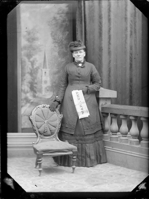 Unidentified woman holding newspaper, wearing fancy black hat, long knee high top which is tight above the hips, long shirt with pleats at the bottom. Salvation Army War Cry
