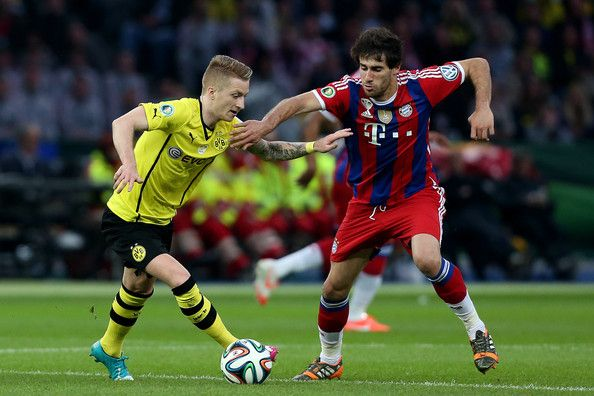 Marco Reus (L) of Dortmund and Javi Martinez of Muenchen vie during the DFB Cup final match 2014 between Borussia Dortmund and Bayern Muenchen at Olympiastadion on May 17, 2014 in Berlin, Germany.
