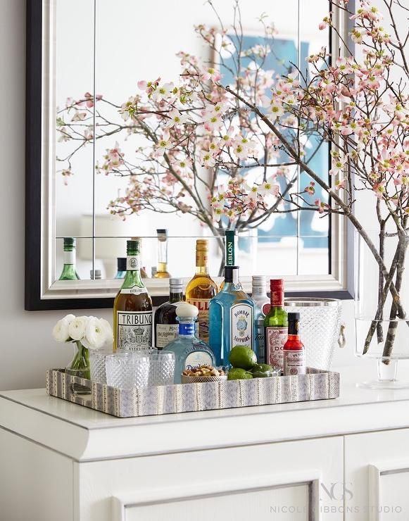 A white dining room bar cabinets is topped with a metal bar tray positioned under a silver and black beveled mirror.