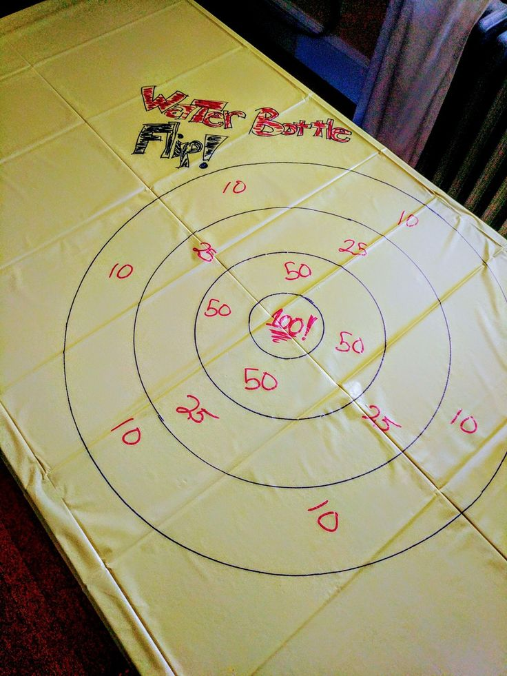 Fun for kids! Play darts' rules with water bottle flip. Dollar store vinyl table cloth and markers make an easy game table!!