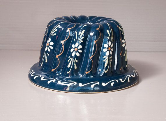 A traditional French Kugelhopf bundt pan from the Alsace region. Deep blue with floral decor, this ceramic cake mold is hand-painted.