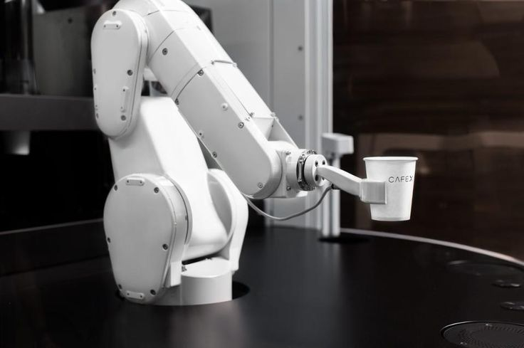 Behind a large pane of curved glass, a six-axis robotic arm swivels back and forth with hot cups of coffee. Two automated coffee machines in the back grind coffee, pull espresso shots and steam milk. The robotic arm -- made by Mitsubishi and designed for industrial usage -- places the cup near the front of the glass to await pick up.