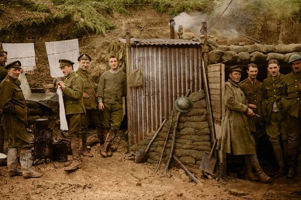 Soldiers stood around inside a trench wait for orders