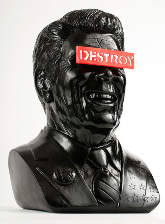 """Smash the state with Kidrobot's exclusive color way of Frank Kozik's newest incendiary statue, """"The Gipper"""". Reminding us the future is stupid, good ole' Ronnie Reagan has been satirically enhanced with an anarchy lapel pin, safety-pin earring and a removable DESTROY sign over his eyes."""