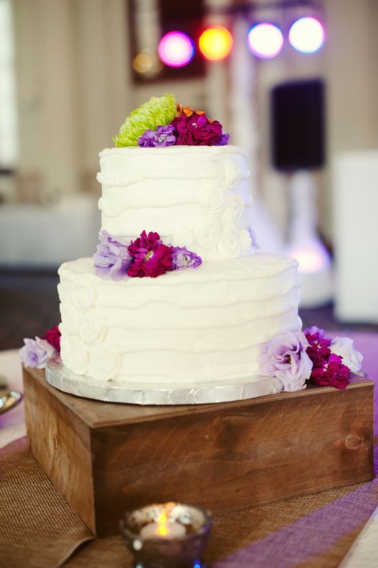 Pops of bright purple and dark red floral wedding cake from Melissa Copeland Photography