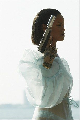 """First off, let's just talk about this outfit. Can we just acknowledge that Rihanna """"woke up"""" wearing a sheer wrap and a full neck of pearls, and she is strolling around her house with a gun? 