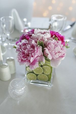 Beautiful blowsy peonies in a vase lined with cut limes for a stunning summer wedding centerpiece idea