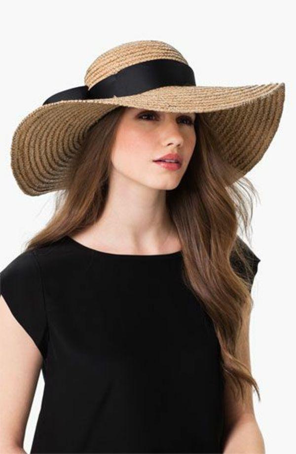 une fille avec un t-shirt noir et chapeau de paille beige avec un ruban noir