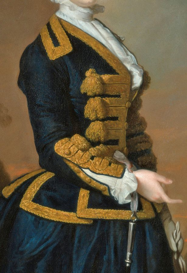 Navy blue Riding habit with elaborate gold frogging, gold braid covered buttons, white shirt with high collar frill, and frill at wrists; gloves; satin ribbon around wrist dangling hunting whistle. Detail from Portrait of a Young Woman of the Fortesque Family of Devon, c.1745, by Thomas Hudson.