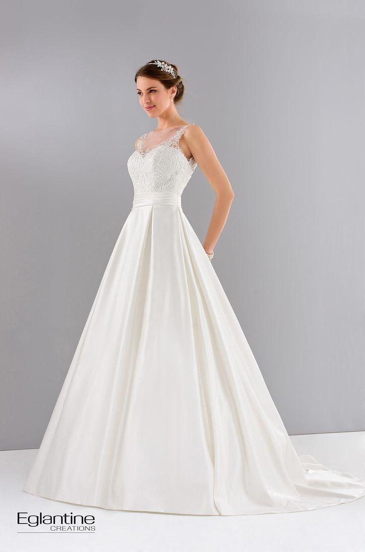 Robe de mariée en satin et dentelle. La robe est constituée d'un buste court habillé de dentelle sur une jupe en satin à plis creux. Boutonnage dos. Disponible en ivoire et en blanc