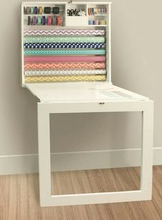 Cutting table mounted on wall above sewing cabinet