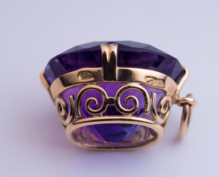 made in Moscow in the 1930s. A 14k gold pendant features a sparkling medium purple cushion-cut Siberian amethyst measuring 16 x 14.1 x 11.2 mm, approximately 14.73 ct. The pendant is marked on frame with early Soviet assay mark for 583 gold standard and maker's mark. Siberian amethysts are no longer mined. They are rare and could be found only in Tsarist era or early Soviet 1930s-1950s jewelry. http://romanovrussia.com