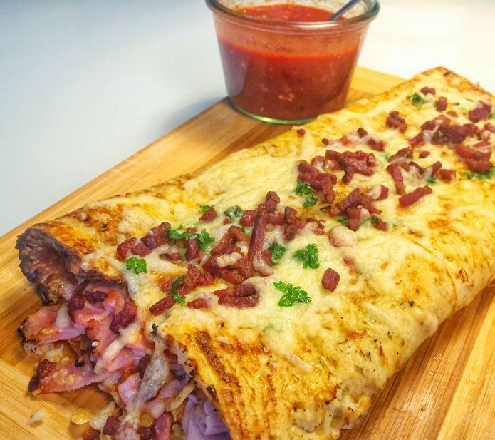 Calzone af blomkål og mozzarella med tomat, skinke, ost og sprød bacon