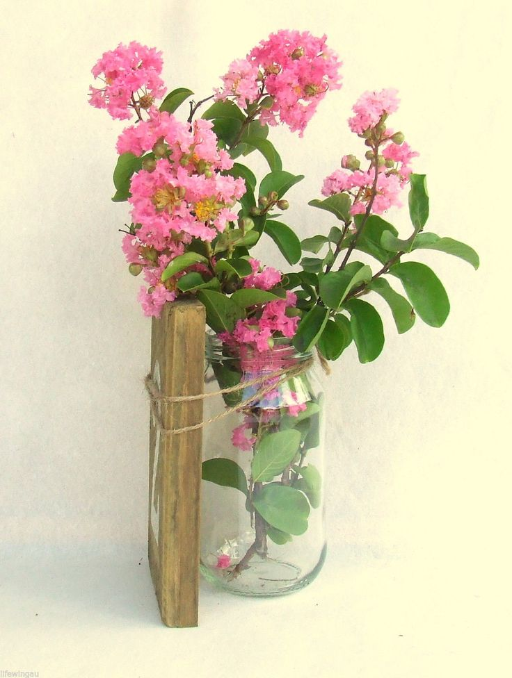 Wooden number tied to jar of flowers
