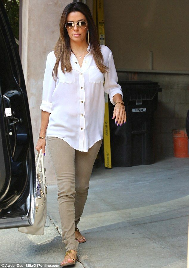 Airport chic: Eva Longoria added some glitz to her otherwise neutral ensemble in the form ...