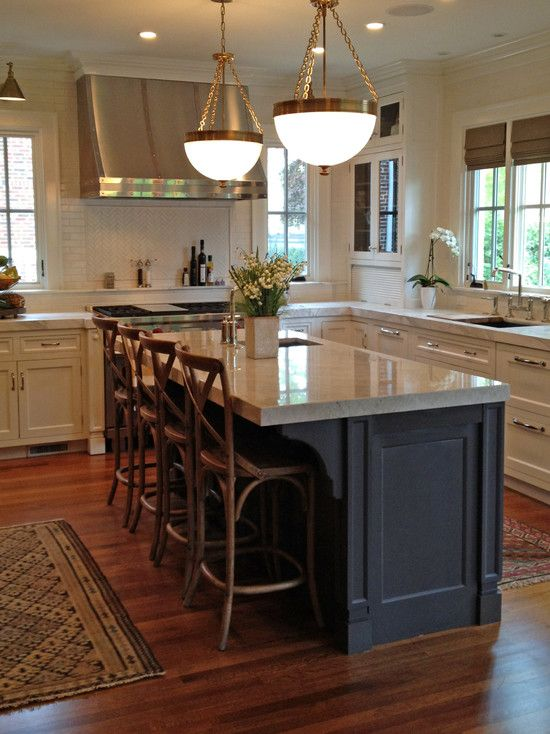 Grand two-tone kitchen design with generous custom white inset cabinets and  upper glass-