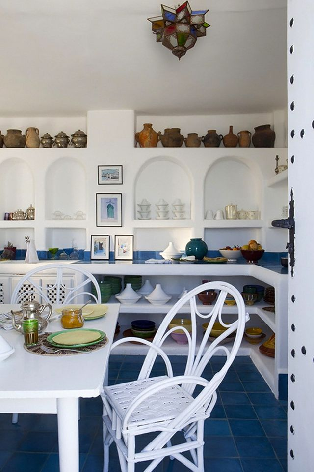Okay, in this photo can we please admire the beautiful blue and white hues that are used.  Theyalmost have a cape cod beach house feel, but done then we see the Moroccan pottery lined on the shelves and the beautiful Moroccan Tea Pot sitting on the table.   Elephant Blanc