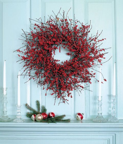 A circle of winterberry branches brightens a mantel scene. Instructions: Cut 40 to 50 branches of winterberries to measure between 10 and 16 inches long. Using green florist wire, attach the larger branches to a 16- to 18-inch wire frame one at a time, overlapping as you go. Continue adding smaller branches until it looks full; use a glue gun when the wiring becomes too difficult.