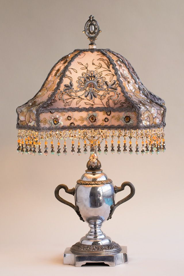 Chrome plated antique lamp reminiscent of a silver tea service holds a hand dyed silver gent silk lampshade the shade is dyed silvery gray and is